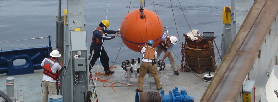 "Melville ""restech"" Drew Cole and deck boss William Ostrom are aided by science team to deploy the main float of the Hybrid Profiler Mooring. (Photo Credit: Station Papa Science Team)"