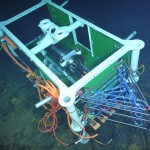Medium-power junction box installed in the ASHES hydrothermal field of Axial Seamount's caldera. The titanium cylinder inside the node frame hosts power converters, data ports, and shore-linked communication capabilities. This J-box also hosts a cabled 3D thermistor array (the triangular-shape frame with blue cables) that was deployed for testing during the expedition. (Photo credit: NSF-OOI/UW/CSSF)
