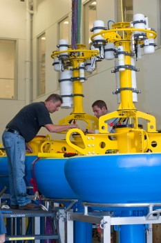 As preparations continue, WHOI Senior Engineering Assistants Jim Dunn (left) and Kris Newhall (right) prepare surface buoys for the Pioneer Array Coastal Profiler Moorings. The buoy towers house electronics and antennas (white cylinders) to enable real-time data transfer and two-way command and control from shore.