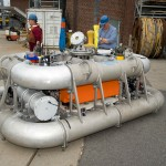 As assembled Multi-Function Node (MFN). Multi-function nodes are prepared on land for pre-deployment testing. Multi-function nodes serve both as the anchor for moorings as well as a platform for mounting oceanographic sensors. They contain a suite of seafloor instruments, platform control and power electronics, and an anchor with recovery floatation (orange).