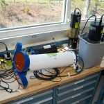 Bench testing of instrumentation in preparation for the OOI Pioneer Array phase-1 deployment. Instruments include an Acoustic Doppler Current Profiler (ADCP) (foreground), fluorometer (left), partial pressure of CO2 in air instrument (back), pH instrument (back right), and partial pressure of CO2 in water instrument (front right, in bucket).
