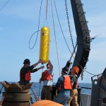 Preparing to deploy the McLane wire-following profiler in 600m of water off the coast of Washington, after attaching it to the mooring wire. The yellow profiler travels up and down in the water column on an inductive wire, collecting oceanographic data. It then communicates that data to the surface via an inductive modem connection through the same wire, and the data are then telemetered to shore via satellite. (Photo credit: Mike Vardaro, Oregon State University)