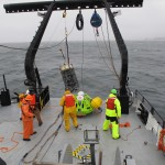 The science party on the R/V Oceanus deploy a WET Labs profiler off of Agate Beach, Oregon as part of the Ocean Observatories Initiative Endurance Array initial deployment cruise. The profiler travels up and down in the water column using a motorized winch and spectra line, collecting oceanographic data and transmitting it to shore. (Photo Credit: Tom Kearney, Oregon State University)