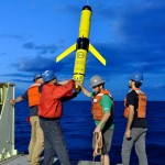 An OOI glider is recovered from the fantail of the R/V Knorr by (L to R) Steve Murphy, John Lund, Jeff Pietro and Aidan Alai. A remotely controled release system is used to deploy a line that is spooled within the glider nose-cone, simplifying recovery. (Photo Credit: Sheri White, WHOI/CGSN)