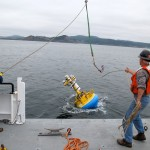 Walt Waldorf (OSU) releases the Endurance Oregon Inshore Surface Mooring buoy into the water offshore of Newport, Oregon. The mooring was deployed on 10 October in 25 meters of water. (Photo Credit: Mike Vardaro, OSU)
