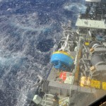 At sea on RV Atlantis sailing under strong winds to the deployment site. Looking down on the surface buoy which was secured to the starboard side of the main deck with the bulwarks removed. (Credit: John Lund, Woods Hole Oceanographic Institution)