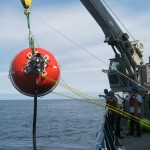 "The 64"" glass sphere, top element of a Flanking Mooring, is deployed over the side. (Photo Credit: OOI Coastal Global Scale Nodes program Argentine Basin deployment team)"
