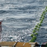 The green glass balls that provide the bottom flotation of a mooring have been deployed. At this point, all the mooring components are in the water and the ship is close to the deployment site where the anchor will be dropped, and the mooring detached from the ship. (Photo Credit: OOI Coastal Global Scale Nodes program Argentine Basin deployment team)