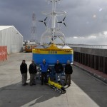 Surface buoy and glider ready for deployment on Southern Ocean cruise. In front, left to right, people from the WHOI team who worked in port in Punta Arenas, Chile: Matt Palanza, Bob Weller, Peter Brickley, Gary Cook, Aidan Alai. (Credit: John Lund, Woods Hole Oceanographic Institution)