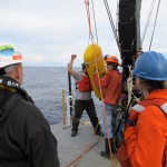 Technician Chris Holm (left) and technician Tully Rohrer (right) prepare to lower the McLane profiler on the Washington offshore profiling mooring. Chris is directing the winch operator. Photo Credit: OOI Endurance Array Program, OSU
