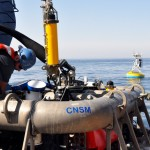 The Mult-Function Node of the Central Coastal Surface Mooring is prepared for deployment by WHOI Engineer Mark Horn while the recently deployed surface buoy trails behind. (Photo: Sheri White, WHOI/CGSN)