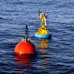 The tower and flotation sphere of the Upstream Inshore Coastal Profiler Mooring wait in calm seas while the anchor is prepared for deployment. (Photo: John Lund, WHOI/CGSN)