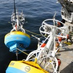 The Central Coastal Surface Mooring buoy is deployed from the starboard rail of the R/V Atlantis. Deck space is tight, and the buoy must be eased out between the crane pedestal and the Inshore buoy. (Photo: Sheri White, WHOI/CGSN)