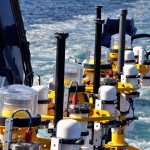 The tower tops of five Coastal Profiler Mooring buoys are lined up along the port rail of the R/V Atlantis in preparation for deployment. Marine lanterns (clear plastic), satellite telemetry systems (white canisters) and radar target enhancers (black pipes) can be identified. (Photo: John Lund, WHOI/CGSN)
