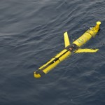 A Global Profiling Glider rests on the sea surface awaiting its first dive after deployment. These gliders, outfitted with muliti-disciplinary instruments, will remain close to the Global Profiler Mooring, and their sampling will include the region between the top of that mooring at roughly 130m depth and the sea surface. The profiling and additional three patrol gliders also have acoustic communication capabilities with the subsurface moorings and will collect their data then send it back when at the surface. (Photo Credit: Sheri N. White)