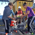 "Mosquito's Onboard - UW undergraduate students Jesse Turner, Lauren Kowalski, and Kearstin Williams help move a ""mosquito"" off of ROPOS's tool sled during Leg 1. This instrument has been measuring the flow of fluids into and out of a methane seep site at Southern Hydrate Ridge since it was installed last year. Credit: Mitch Elend, University of Washington."