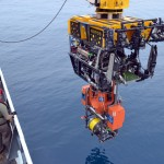 Slope Base Surface Profiler Lowered into the Water - The Slope Base Surface Profiler is lowered into the water attached to the ROV ROPOS. ROPOS will install the Surface Profiler 200 meters below the surface. Photo Credit: Mitch Elend, University of Washington; V15.