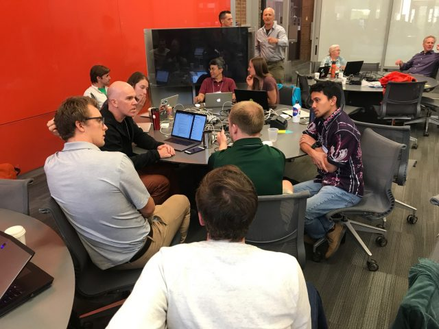 Two groups deep in conversation about their work on data validation and simplified data access. Credit: Rachael Murray, eScience Institute